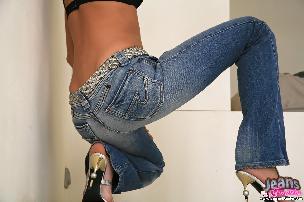 Sexy girl blue jeans undressing showing stock photo
